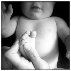 main massant le pied d'un nouveau-né