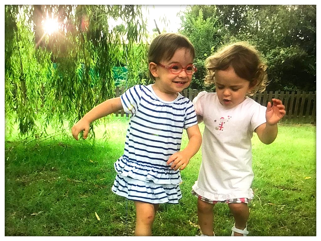 deux petites filles courant sur la pelouse en souriant